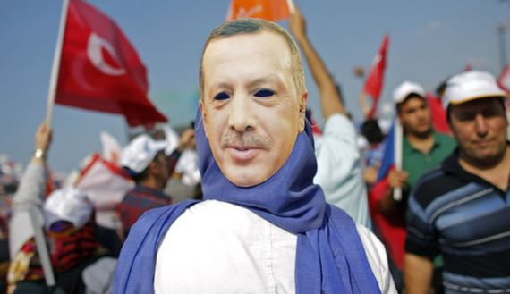 A supporter wears a mask showing Turkish PM Erdogan during a rally of ruling AK party in Istanbul
