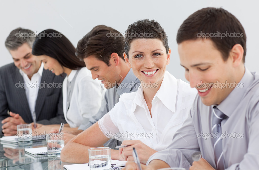 International business people taking notes in a meeting