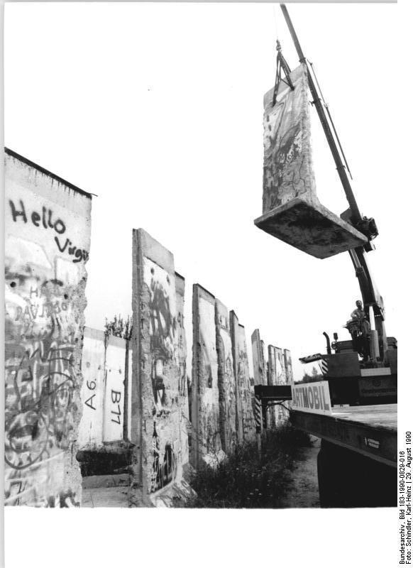 """ADN-Karl-Heinz Schindler-29.8.90-Berlin: Ein Stück Berliner Mauer für die Kennedys- Das Segment der Berliner Mauer, ordentlich mit der Nummer A 8 katalogisiert, schwebt vom Lagerplatz der NVA bei Bernau. Es wird nach Übersee verschifft werden. Empfänger ist die Schwester des ehemaligen US-Präsidenten John F. Kennedy, Jean Smith-Kennedy. Ihr wird das 2,6 Tonnen schwere und 3,60 Meter hohe sowie 1,20 Meter breite Stück der """"Berlin wall"""" als Spende für die John-F.-Kennedy-Bibliothek in Boston überlassen."""