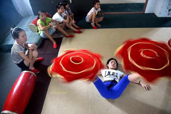 06 Aug 2015, China --- (150806) -- LINQUAN, Aug. 6, 2015 (Xinhua) -- A girl practises basic skills at an acrobatic school in Linquan, east China's Anhui Province, Aug. 6, 2015. Acrobatics has become a major way for most local people to acquire a well-off life, and plenty of leftover children here are sent to acrobatic school at a very young age. (Xinhua/Liu Junxi) (hgh) --- Image by © Liu Junxi/Xinhua Press/Corbis
