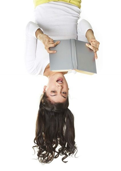 Surprised teen reading book in an unusual position, isolated on white