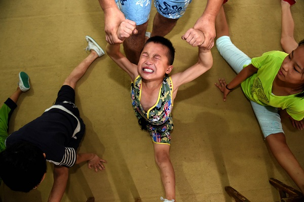 06 Aug 2015, China --- (150806) -- LINQUAN, Aug. 6, 2015 (Xinhua) -- Students practise basic skills at an acrobatic school in Linquan, east China's Anhui Province, Aug. 6, 2015. Acrobatics has become a major way for most local people to acquire a well-off life, and plenty of leftover children here are sent to acrobatic school at a very young age. (Xinhua/Liu Junxi) (hgh) --- Image by © Liu Junxi/Xinhua Press/Corbis