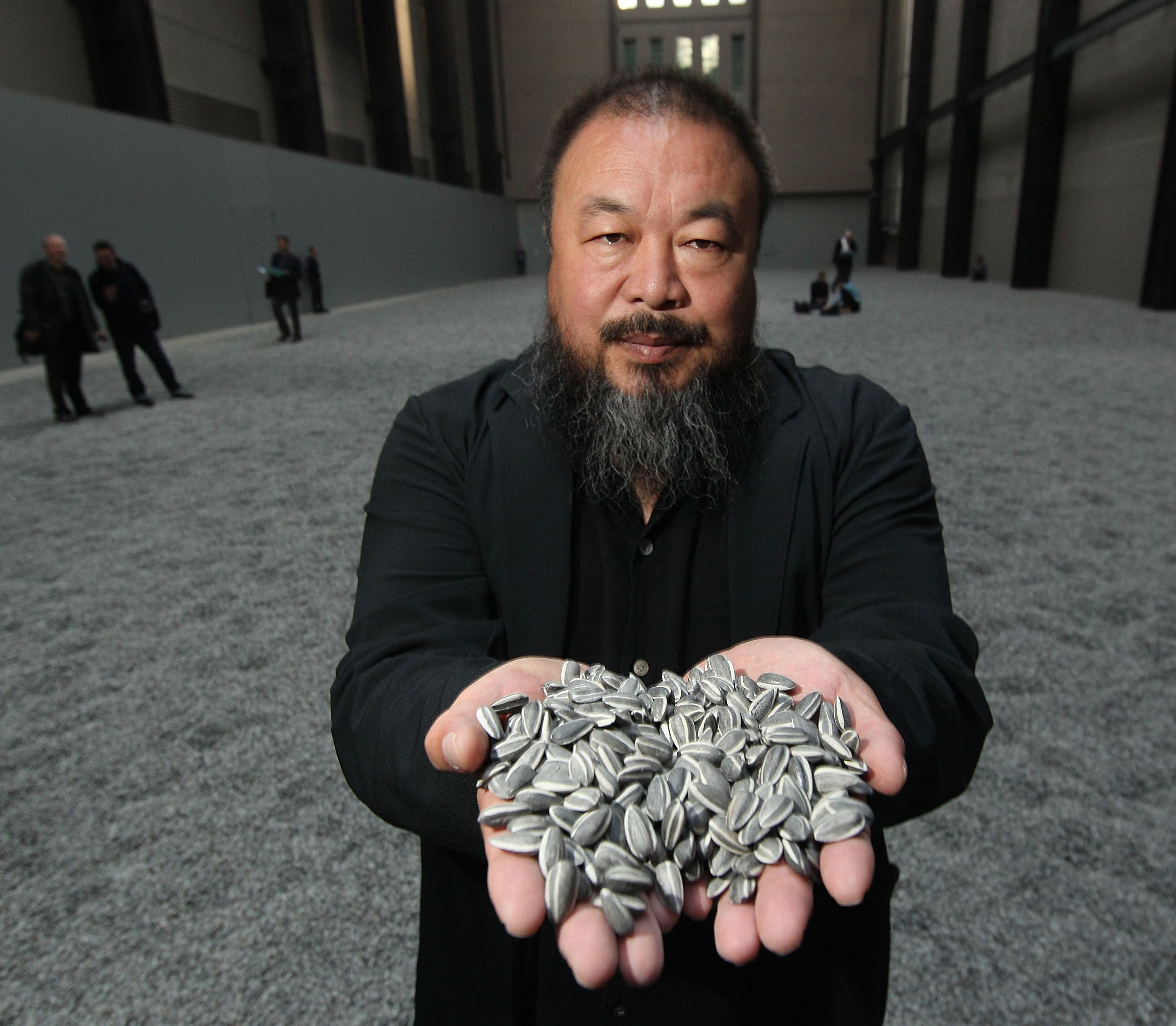 LONDON, ENGLAND - OCTOBER 11:  Chinese Artist Ai Weiwei holds some seeds from his Unilever Installation 'Sunflower Seeds'  at The Tate Modern on October 11, 2010 in London, England. The sculptural installation comprises 100 million handmade porcelain replica sunflower seeds. Visitors to the Turbine Hall  will be able to walk on the work - which opens on October 12, 2010 and runs until May 2, 2011.  (Photo by Peter Macdiarmid/Getty Images)
