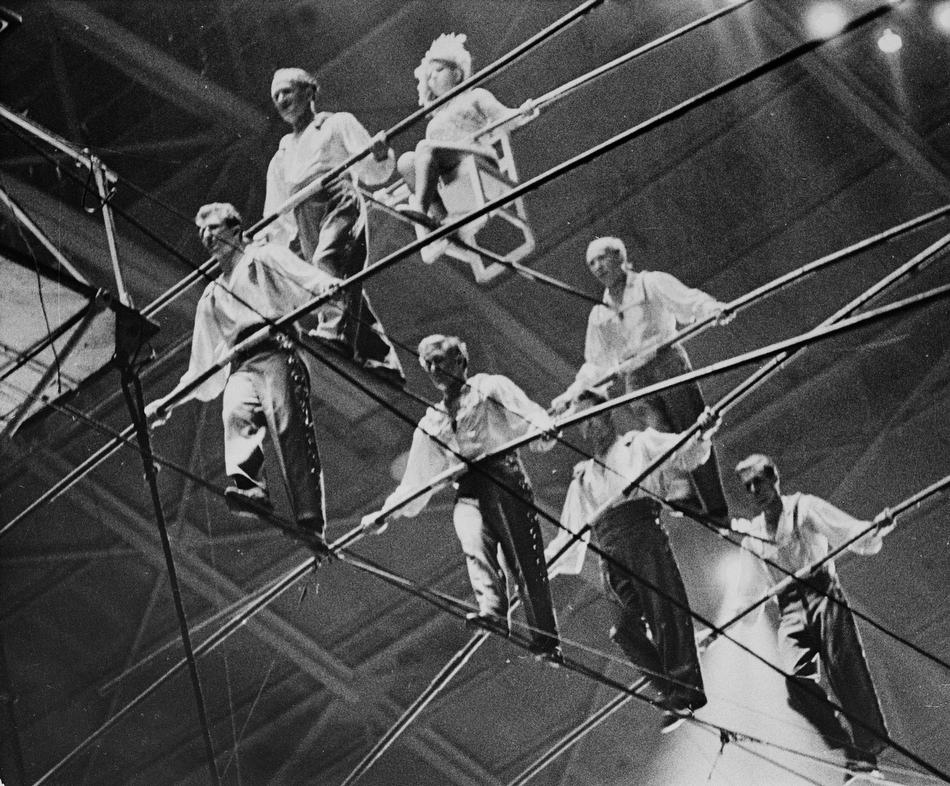 The Great Wallendas circus troupe walk the high wire during their three-tier seven-man pyramid performance at the State Fair Coliseum in Detroit, Michigan on Jan. 30, 1962.  From left to right, bottom row, are, Dieter Schepp, 23; Mario Wallenda, 21; Richard Faughnan, 29; Gunther Wallenda, 42.  Second row, left to right, Karl Wallenda, 57; Herman Wallenda, 60.  Sitting on chair is Jana Schepp, 17.  Karl's son-in-law Faughnan and nephew Schepp were killed when the pyramid formation collapsed and the performers fell to the ground.  Dieter's sister Jana and Karl's son Mario were injured.  (AP Photo)