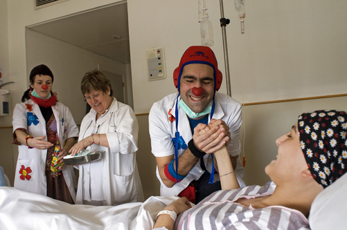 Hospital clowns joke with a cancer patient.