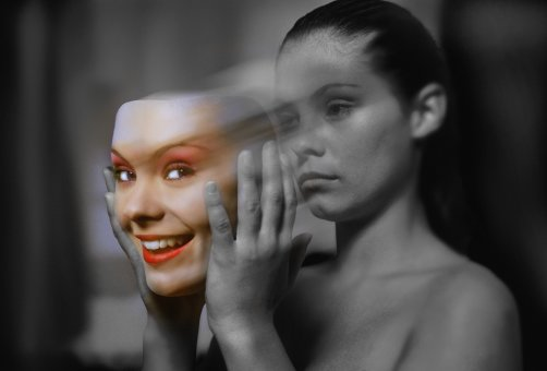 Young woman holding smiling face (digital composite)