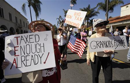 Anita Dwyer (L) and Bea Severson hold signs as they participate in a rally and march in protest of higher taxes in Santa Barbara, California