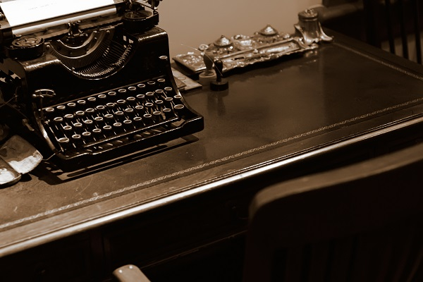 It is an old typewriter for bank on the desk.