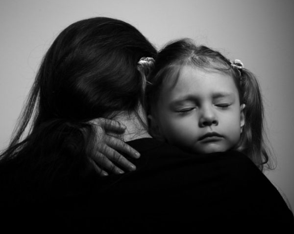 Depression daughter hugging her mother with sad face. Closeup portrait black and white
