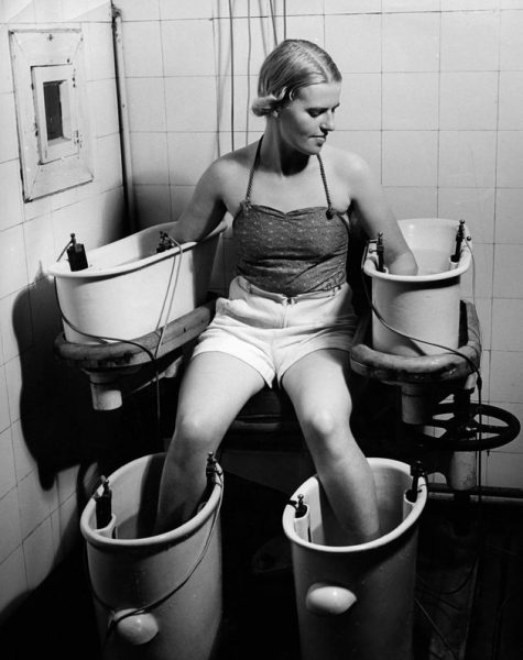 (GERMANY OUT) Four-cell galvanic bath: A young woman holds her arms and legs in four water bathes with electric current, this procedure has positive effect on blood circulation - around 1938 - Photographer: Hedda Walther - Published by: 'Die Dame' 21/1938 Vintage property of ullstein bild  (Photo by Hedda Walther/ullstein bild via Getty Images)