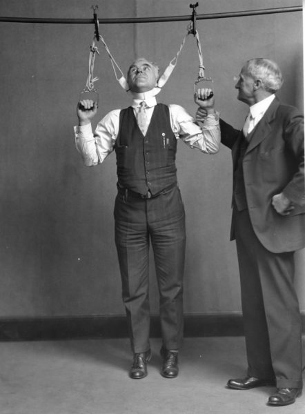 Post Office Department Inspector DF Angier (left) and Dr LF Kebler, formerly of the Food & Drug Adminstration, are trying out a stretching device alleged to effect an increase in height from 2 to 6 inches, Washington DC, February 4, 1931. (Photo by PhotoQuest/Getty Images)