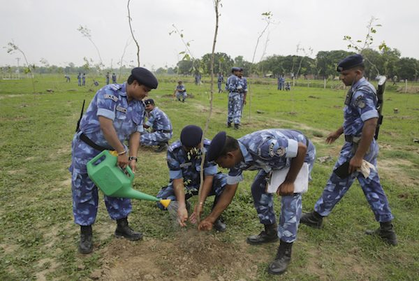Indian para-military force soldiers plant saplings on the outskirts of Allahabad, India, Monday, July 11, 2016. Hundreds of thousands of people in India's most populous state Uttar Pradesh are jostling for space as they attempt to plant 50 million trees over the next 24 hours in hopes of setting a world record. (AP Photo/Rajesh Kumar Singh)