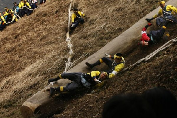 """Shrine parishioners fall off a log called """"Onbashira"""" when riding it down a hill as part of delivering it to a Shinto shrine during the Onbashira Festival in Shimosuwa, east of Tokyo, Japan, Friday, April 9, 2010. Those parishioners carry 16 logs to the four Suwa Grand Shrines, four logs to each shrine, to spiritually renew the shrines in the two-and-a-half-month-long festival. The festival takes place every seven years. (AP Photo/ Hiro Komae)"""