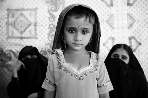 A young girl poses while her mother waits to see a doctor in a tent camp for flood victims. Sukkur, Pakistan, 2010