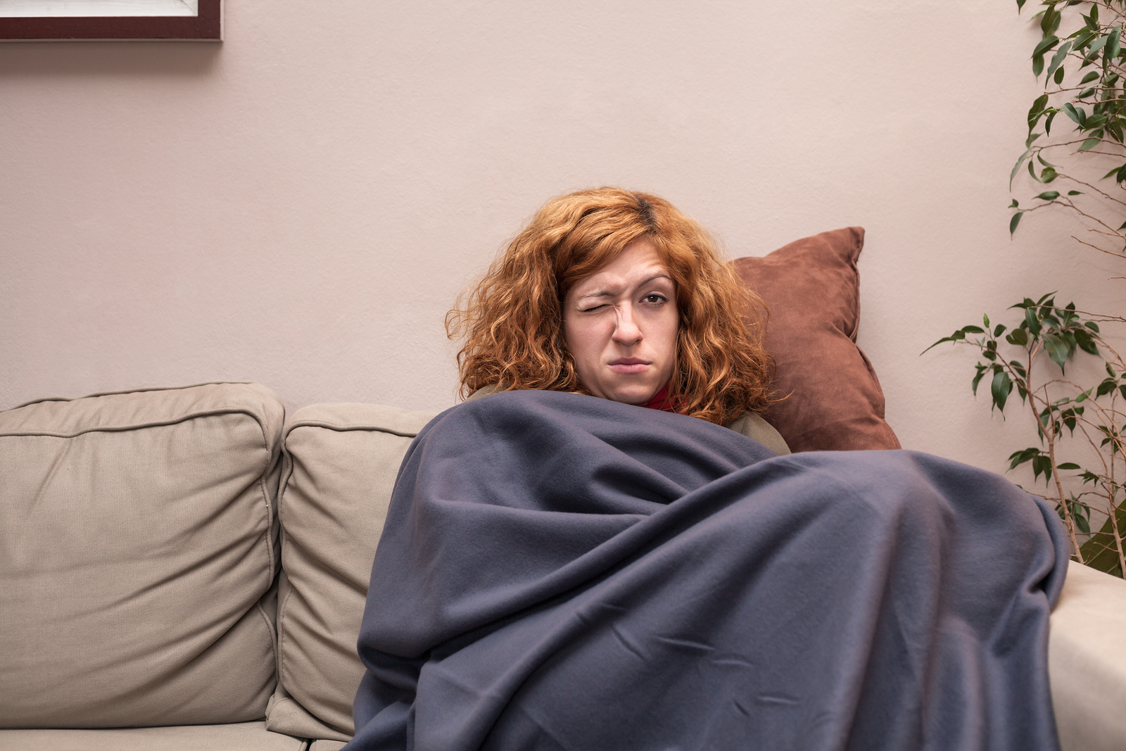 Tired Woman With A Cold Resting On Sofa