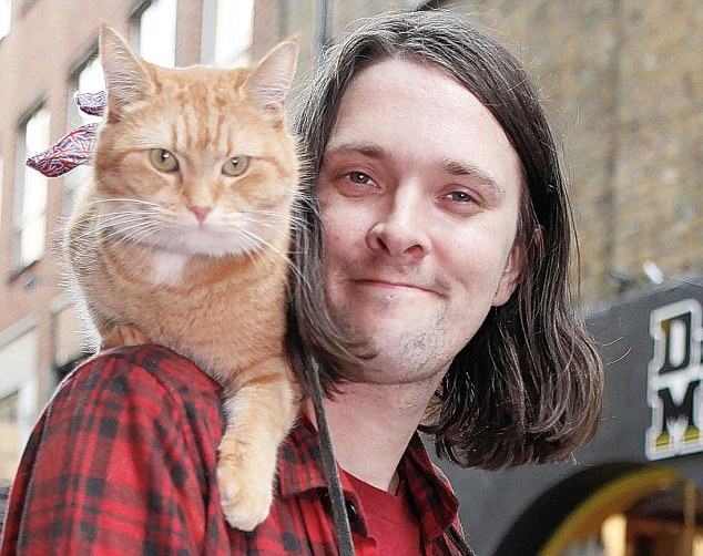 James Bowen and Bob the cat busking in Covent Garden.
