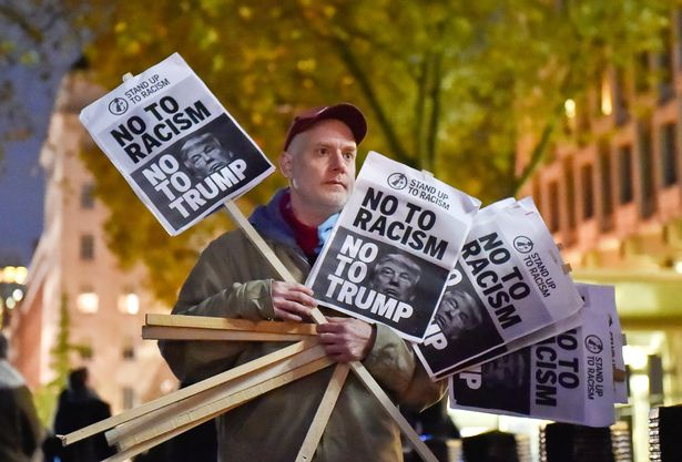 A-man-holds-placards-at-an-anti-racism-protest-against-US-President-elect-Donald-Trump-outside-of