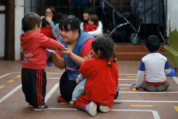 """Noelia Garella (C), a kindergarten teacher born with Down Syndrome, plays with children at the Jeromito kindergarten in Cordoba, Argentina on September 29, 2016. When Noelia Garella was a child, a nursery school rejected her as a """"monster."""" Now 31, she is in a class of her own. In the face of prejudice, she is the first person with Down syndrome to work as a kindergarten teacher in Argentina -- and one of few in the world.  / AFP / DIEGO LIMA        (Photo credit should read DIEGO LIMA/AFP/Getty Images)"""