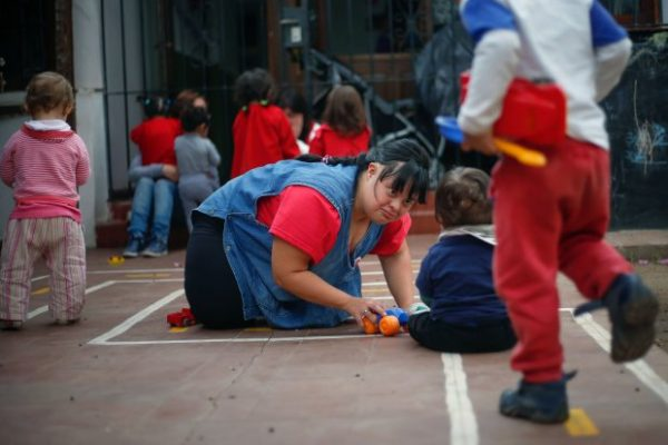"""Noelia Garella (C), a kindergarten teacher born with Down Syndrome, plays with children at the Jeromito kindergarten in Cordoba, Argentina on September 29, 2016. When Noelia Garella was a child, a nursery school rejected her as a """"monster."""" Now 31, she is in a class of her own. In the face of prejudice, she is the first person with Down syndrome to work as a kindergarten teacher in Argentina -- and one of few in the world.  / AFP PHOTO / DIEGO LIMADIEGO LIMA/AFP/Getty Images"""