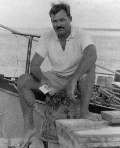 EH6670P   1930s Ernest Hemingway sitting on a dock next to the Pilar, 1930s.  Photographer unknown in the Ernest Hemingway Collection of the John F. Kennedy Presidential Library and Museum, Boston.