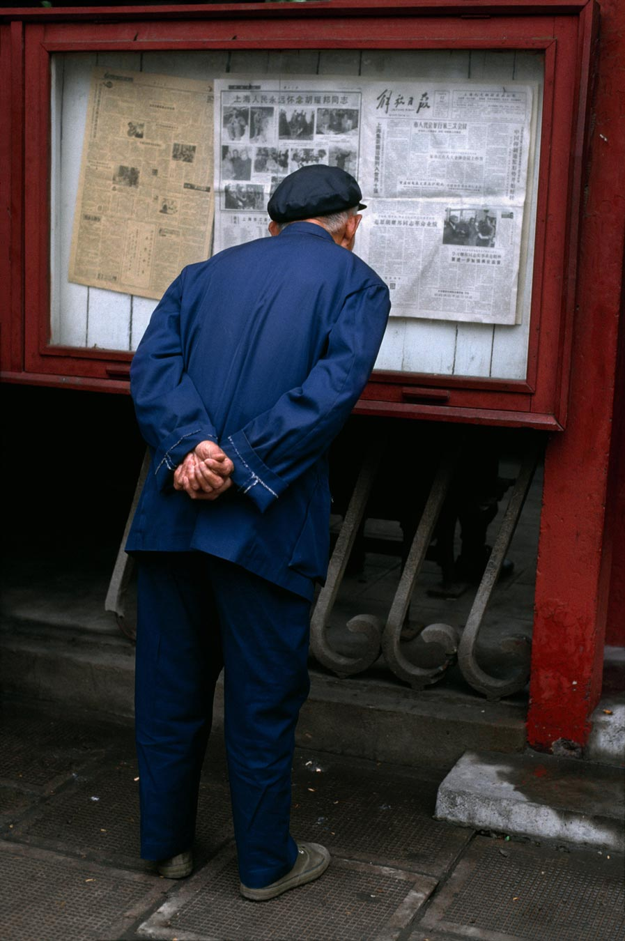 An elderly man reads a posting of the newspaper, China, 04/1989