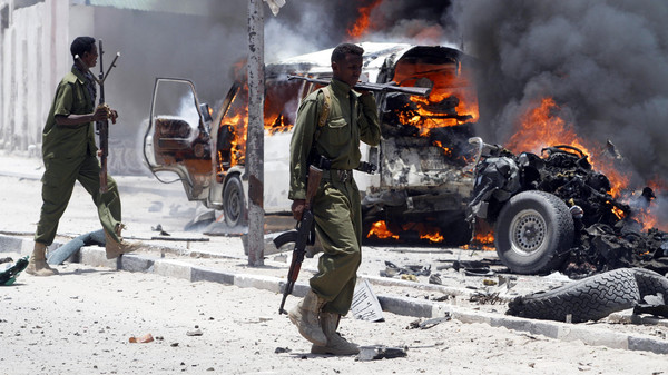Policemen walk past the scene of an explosion near the presidential palace in Somalia's capital Mogadishu