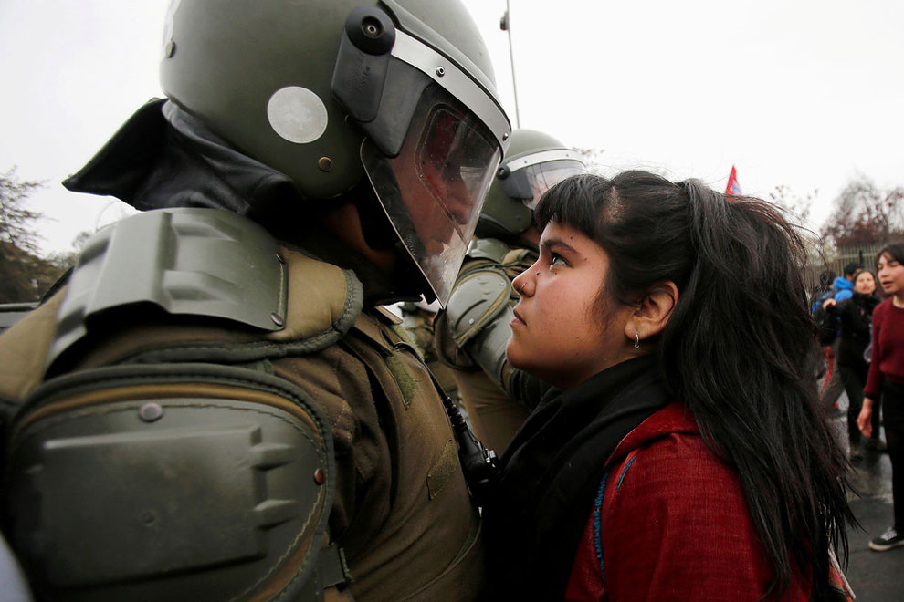A demonstrator looks at a riot policeman during a protest marking the country's 1973 military coup in Santiago, Chile September 11, 2016.