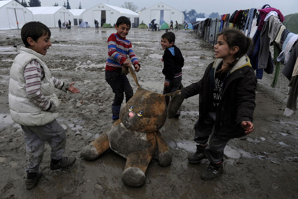 Refugee children play with a stuffed toy at a muddy makeshift camp at the Greek-Macedonian border, near the village of Idomeni, Greece March 15, 2016.