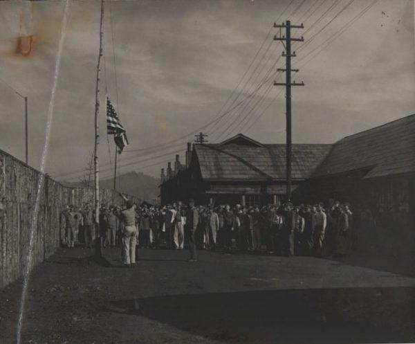 1087px-Flag_Raising_After_POW_Camp_Liberation_1945_9044196508-640x530