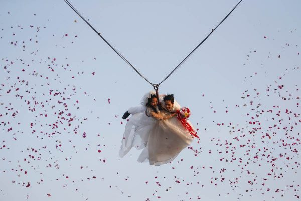a-bride-and-groom-fly-while-attached-to-cables-during-a-wedding-ceremony-ahead-of-valentines-day-at-a-resort-in-ratchaburi-province-thailand
