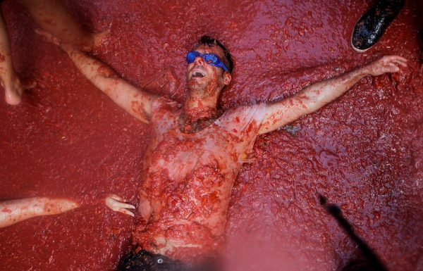 a-man-lies-in-tomato-pulp-during-the-annual-tomatina-festival-in-bunol-near-valencia-spain