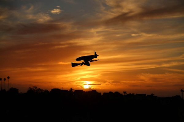 a-remote-controlled-plane-in-the-form-of-a-witch-flies-over-a-neighborhood-as-the-sun-sets-during-halloween-in-encinitas-california