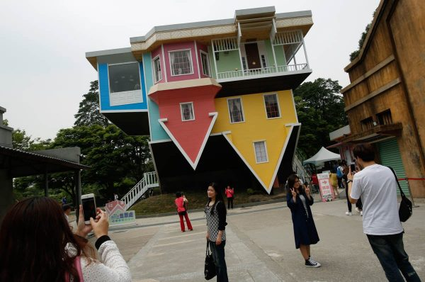visitors-pose-in-front-of-a-three-story-upside-down-family-sized-house-at-the-huashan-creative-park-in-taipei-taiwan