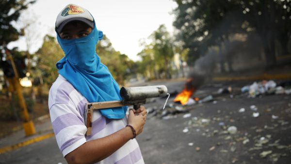 A demonstrator stands guard with a rudimentary mortar in front of a burning barricade during protests against Nicolas Maduro's government in San Cristobal, about 410 miles (660 km) southwest of Caracas, February 26, 2014. Pope Francis called on Wednesday for an end to violence in Venezuela that has killed at least 13 people and urged politicians to take the lead in calming the nation's worst unrest for a decade. REUTERS/Carlos Garcia Rawlins (VENEZUELA - Tags: POLITICS CIVIL UNREST) - RTR3FRE0