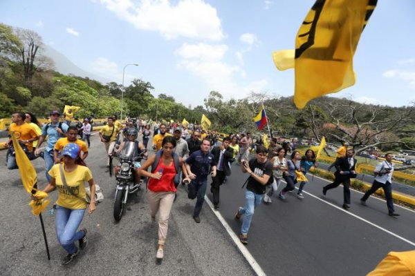 Opposition supporters run as they block a highway during a protest against Venezuela's President Nicolas Maduro's government in Caracas, Venezuela April 3, 2017. REUTERS/Carlos Garcia Rawlins