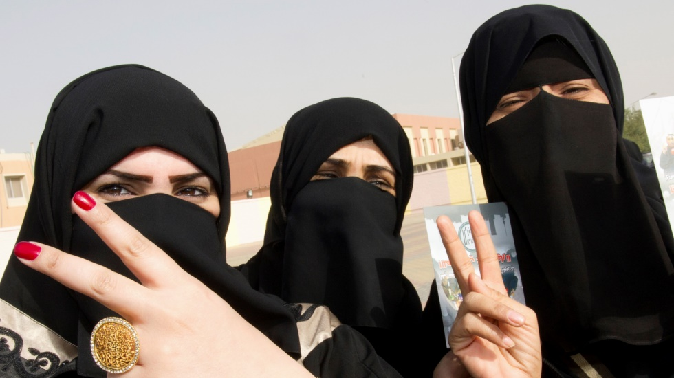 Kuwaiti girls give a victory sign as they stand in front of a polling station in Jahra February 2, 2012. Kuwaitis headed to the polls on Thursday for the fourth time in six years in a snap parliamentary election in which opposition candidates expect to expand their influence and push for change in the oil-exporting Gulf Arab state. REUTERS/Stephanie McGehee (KUWAIT - Tags: POLITICS ELECTIONS)