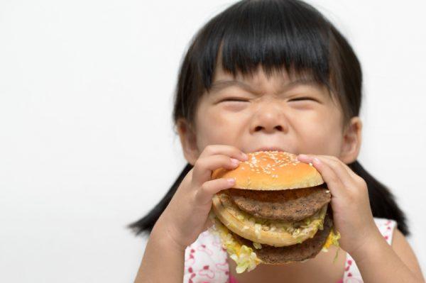 Kid eating big burger