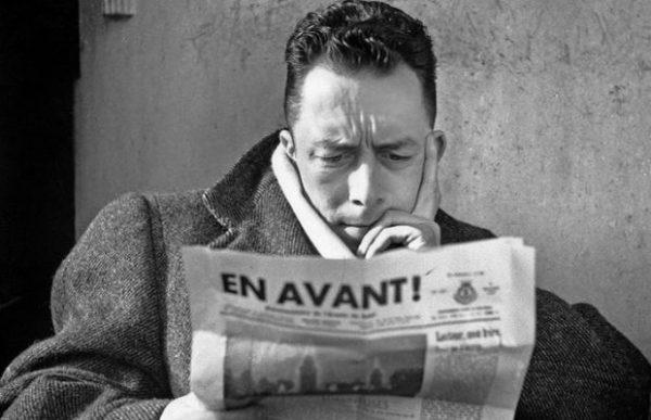 """Albert Camus (1913-1960) journaliste redacteur en chef du journal Combat de 1944 a 1947 ici lisant le journal """"En Avant !"""" journal de l'Armee du Salut au cafe Les Deux Magots a Paris en 1945    --- Albert Camus (1913-1960) french writer here writing a paper in 1945"""