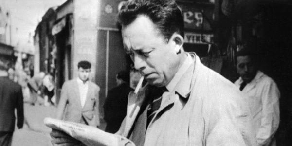 """Attitude familière - lisant un journal, cigarette aux lèvres - d'Albert Camus, écrivain français, journaliste, philosophe et Prix Nobel de littérature 1957. A file picture taken in 1953, shows French writter and 1957 literature Nobel prize laureate Albert Camus (1913-1960), reading a newspaper in Paris. France's President Nicolas Sarkozy said on November 19, 2009 in Brussels that It would be an """"extraordinary symbol"""" to """"burry Albert Camus at the Pantheon"""", 50 years after Camus' death. The Pantheon, located in Latin Quarter in Paris and was originally built as a church, is a place where are buried great men, honoured by the Nation. AFP PHOTO"""