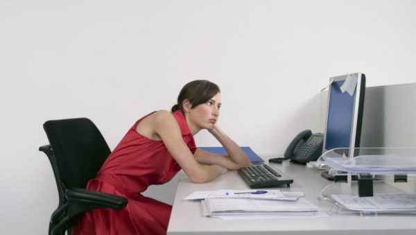 Side view of a bored female office worker looking at notes on computer monitor at desk