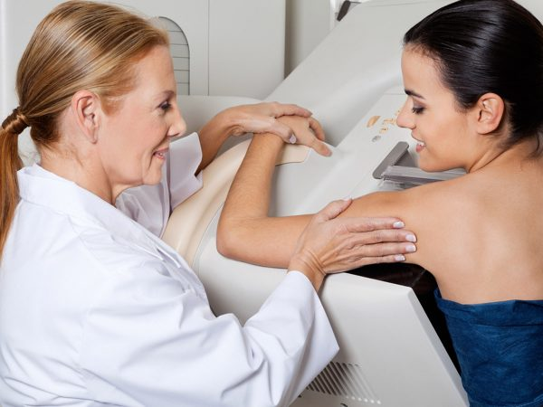 Mature female doctor assisting young patient during mammography; Shutterstock ID 123448411; PO: dicembre