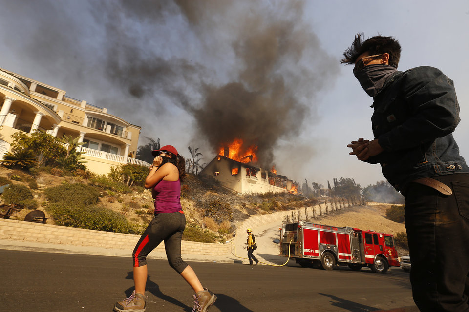 VENTURA, CA - DECEMBER 05: Amanda Leon and husband Johnny Leon watch as Firefighters fight to save multi-million dollar homes along Cobblestone Drive near Foothill Road and North Victoria Avenue Tuesday midday after a fast-moving, wind-fueled wildfire swept into Ventura destroying many homes early Tuesday, burning over 45,000 acres, destroying homes and forcing 27,000 people to evacuate.  (Photo by Al Seib/Los Angeles Times via Getty Images)