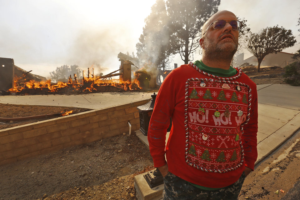 VENTURA, CA - DECEMBER 05: Wearing his Christmas garb Justin Ekback watches as Firefighters fight to save multi-million dollar homes along Cobblestone Drive near Foothill Road and North Victoria Avenue Tuesday midday after a fast-moving, wind-fueled wildfire swept into Ventura destroying many homes early Tuesday, burning over 45,000 acres, destroying homes and forcing 27,000 people to evacuate.  (Photo by Al Seib/Los Angeles Times via Getty Images)