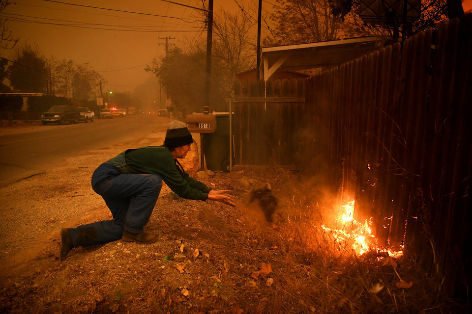 VENTURA, CA - DECEMBER 5: Carolyn Potter tries to save her house as she throws dirt on her fence along Nye Road Thomas Fire in Casita Springs in Ventura County Tuesday. (Photo by Wally Skalij/Los Angeles Times via Getty Images)