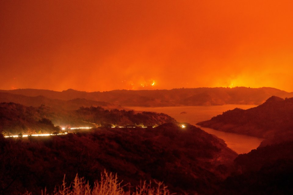 CALIFORNIA, USA - DECEMBER 5: Cars drive around Lake Casitas and away from the Thomas Fire as it crests a mountains near the lake on December 5, 2017 in Ventura, California, United States. The fire has consumed over 50,000 acres according to the California Department of Forestry and Fire protection. (Photo by Justin L. Stewart/Anadolu Agency/Getty Images)