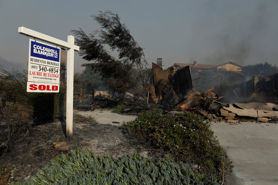 A real estate sign post is seen next to the remains of a home, after it burned to the ground, during a wind-driven wildfire in Ventura, California, U.S., December 5, 2017. REUTERS/Mike Blake